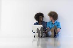 Couples multi-ethniques se reposant sur le plancher avec un ordinateur portable et un comprimé Photographie stock libre de droits