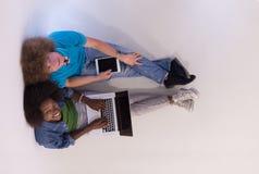 Couples multi-ethniques se reposant sur le plancher avec un ordinateur portable et un comprimé Images stock