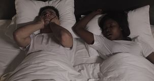 Couples multi-ethniques se situant dans le lit ensemble L'homme souffre de son associé ronflant dans le lit Couplez le mode de vi clips vidéos