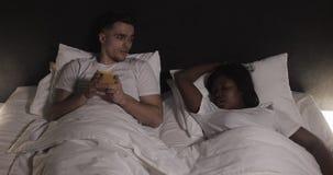 Couples multi-ethniques se situant dans le lit ensemble L'homme souffre de son associé ronflant dans le lit Couplez le mode de vi banque de vidéos