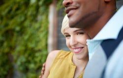 Couples multiculturels attrayants et élégants dans l'amour caressant par une barrière dans un environnement urbain rempli de lier Images libres de droits