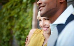 Couples multiculturels attrayants et élégants dans l'amour caressant par une barrière dans un environnement urbain rempli de lier Photo libre de droits