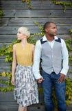 Couples multiculturels attrayants et élégants dans l'amour tenant des mains par une barrière dans un environnement urbain rempli  Photographie stock libre de droits