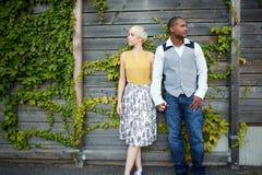 Couples multiculturels attrayants et élégants dans l'amour tenant des mains par une barrière dans un environnement urbain rempli  Image stock