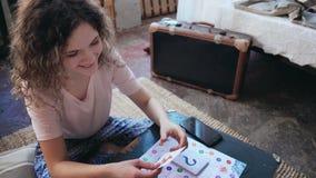Couples multiraciaux dans des pyjamas jouant le jeu de société L'homme dessine sur la main de la femme s entendue, fait la tâche  Photos libres de droits