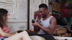 Couples multiraciaux dans des pyjamas sur le lit dans le matin Le jeune homme prenant des photos sur le vieux photocamera, femme  banque de vidéos