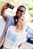 Couples multiraciaux de sourire de jeunes prenant le foto par le smartphone Photo stock