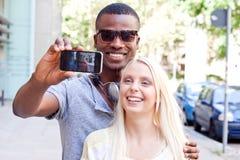 Couples multiraciaux de sourire de jeunes prenant le foto par le smartphone Photos stock