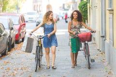 Couples multiraciaux des amis avec des vélos Images stock