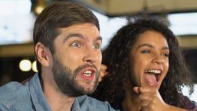 Couples multiraciaux encourageant pour le but préféré d'équipe, match de observation dans le bar banque de vidéos