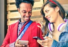 Couples multiraciaux flirtant avec des nombres de smartphone Photo stock