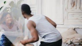 Couples multiraciaux heureux courus l'un après l'autre et oreillers de combat L'homme et la femme dans des pyjamas ont l'amusemen banque de vidéos