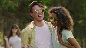 Couples multiraciaux prenant le selfie et regardant des photos sur le smartphone, bonheur banque de vidéos