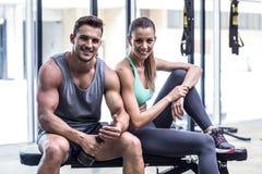 Couples musculaires de sourire se reposant sur le banc photographie stock