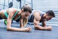 Couples musculaires faisant des exercices de parquet photographie stock libre de droits