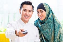 Couples musulmans asiatiques commutant la TV avec à télécommande Photographie stock