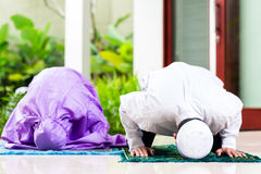 Couples musulmans asiatiques, homme et femme, priant à la maison photo libre de droits