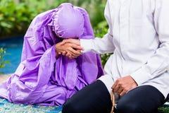 Couples musulmans asiatiques, homme et femme, priant à la maison Photos libres de droits