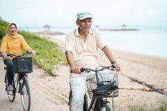 Couples musulmans supérieurs heureux exerçant la bicyclette de monte ensemble photographie stock libre de droits