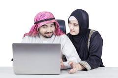 Couples musulmans utilisant l'ordinateur portable Photo stock