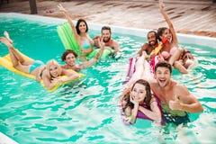 Couples nageant dans la piscine et ayant l'amusement Photos stock