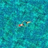 Couples naviguants au schnorchel dans l'eau de mer Vue d'un bourdon Image stock