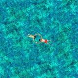 Couples naviguants au schnorchel dans l'eau de mer Vue d'un bourdon Photo libre de droits