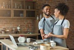 Couples noirs affectueux faisant cuire la pâtisserie dans la cuisine de grenier Photographie stock