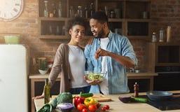 Couples noirs affectueux faisant cuire la salade verte dans la cuisine Photo stock