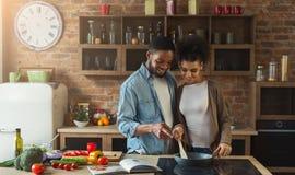 Couples noirs affectueux préparant le repas ensemble dans la cuisine moderne photo stock