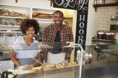 Couples noirs attendant derrière le compteur à une barre de sandwich image stock