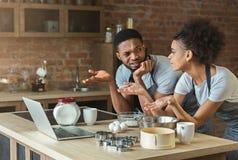 Couples noirs confus faisant cuire la pâtisserie avec la recette sur l'ordinateur portable Photographie stock