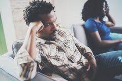 Couples noirs contrariés par jeunes Homme bouleversé ignoré par l'associé à la maison dans le salon Argumentation africaine améri Images libres de droits