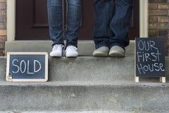 Couples noirs et blancs devant la nouvelle maison Photographie stock libre de droits