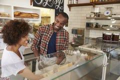 Couples noirs fonctionnant derrière le compteur à une barre de sandwich photos stock