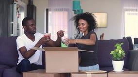Couples noirs heureux déballant la boîte ou colis discutant la conception intérieure clips vidéos