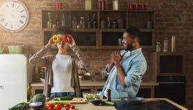 Couples noirs heureux faisant cuire et ayant l'amusement dans la cuisine Photographie stock libre de droits