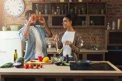 Couples noirs heureux faisant cuire la nourriture saine ensemble Photo stock