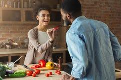 Couples noirs heureux faisant cuire la nourriture saine ensemble Image libre de droits
