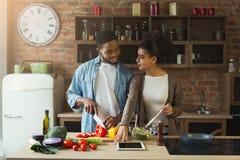 Couples noirs heureux faisant cuire la nourriture saine ensemble Image stock