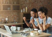 Couples noirs heureux faisant cuire la pâtisserie regardant sur l'ordinateur portable Photo libre de droits