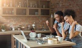 Couples noirs heureux faisant cuire la pâtisserie regardant sur l'ordinateur portable Photo stock