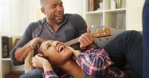 Couples noirs heureux se trouvant sur le divan avec l'ukulélé Photographie stock libre de droits