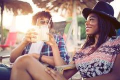Couples noirs heureux sur la plage tout en détendant sur leurs chaises de plate-forme images stock