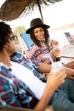 Couples noirs heureux sur la plage tout en d?tendant sur leurs chaises de plate-forme photo libre de droits