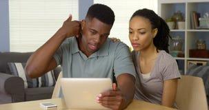 Couples noirs parlant au docteur au sujet de la douleur cervicale au-dessus de la tablette Images libres de droits