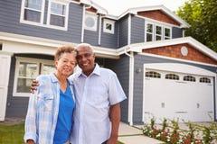 Couples noirs supérieurs debout en dehors d'une grande maison suburbaine Photographie stock