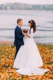 Couples nuptiales de jeunes nouveaux mariés jugeant leurs mains l'automne au bord du lac complètement des feuilles oranges Photos stock