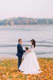 Couples nuptiales de jeunes nouveaux mariés posant l'automne au bord du lac complètement des feuilles oranges Photographie stock