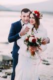 Couples nuptiales de jeunes nouveaux mariés posant sur Pebble Beach près de la rivière de montagne Image stock